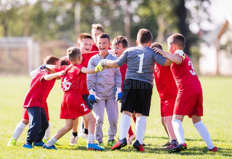 Kids soccer football - children players celebrating after victo. Kids soccer football - young children players celebrating in hug after victory stock photo