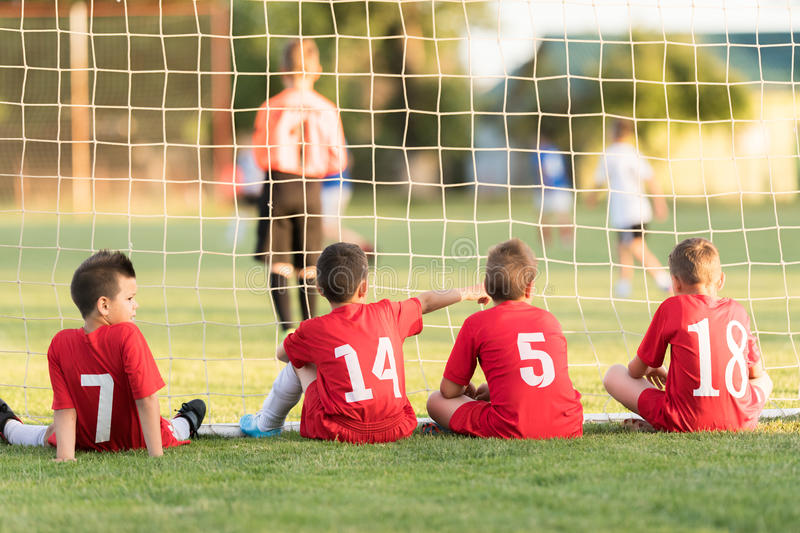 Kids soccer players sitting behind goal watching football match. Kids soccer players sitting in out behind goal watching football match royalty free stock images