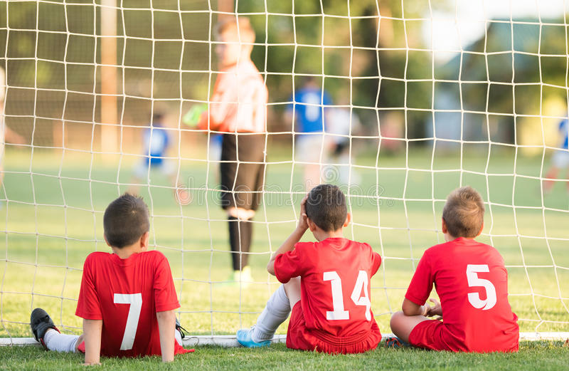 Kids soccer players sitting behind goal watching football match. Kids soccer players sitting in out behind goal watching football match royalty free stock image