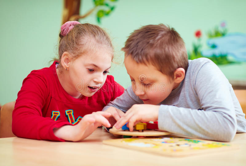 Kids with special needs develop their fine motor skills in daycare rehabilitation center. Cute kids with special needs develop their fine motor skills in daycare stock photo