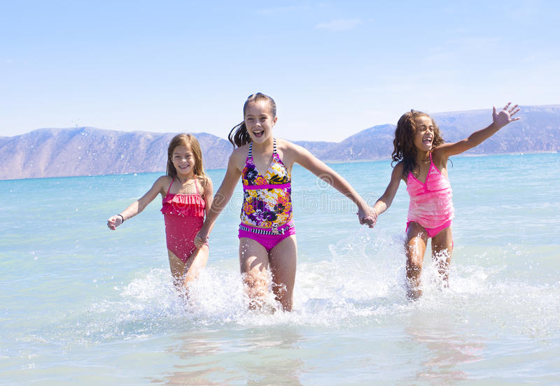 Kids splashing at the beach. Three kids splashing in the water and playing in the ocean while on vacation royalty free stock photography