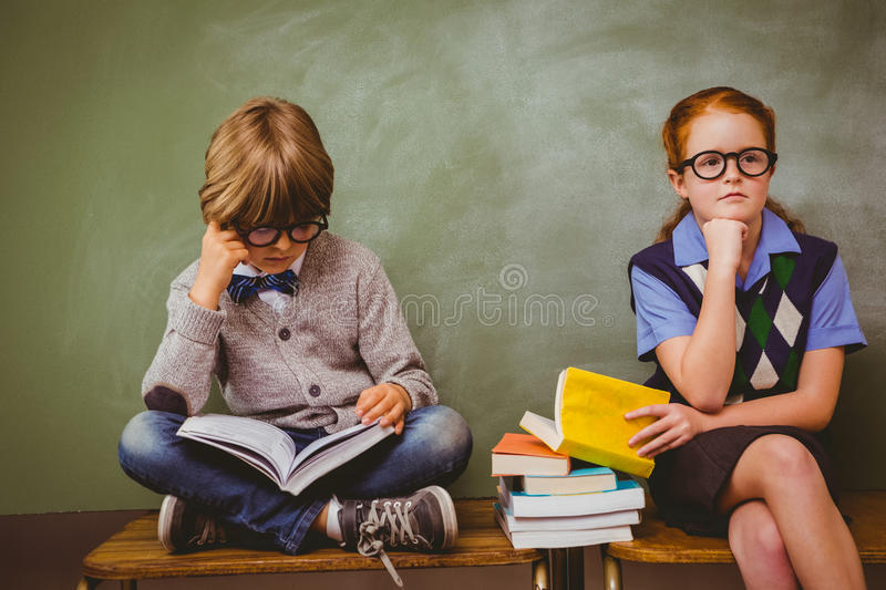Kids with stack of books in classroom. Little school kids with stack of books in classroom royalty free stock photos