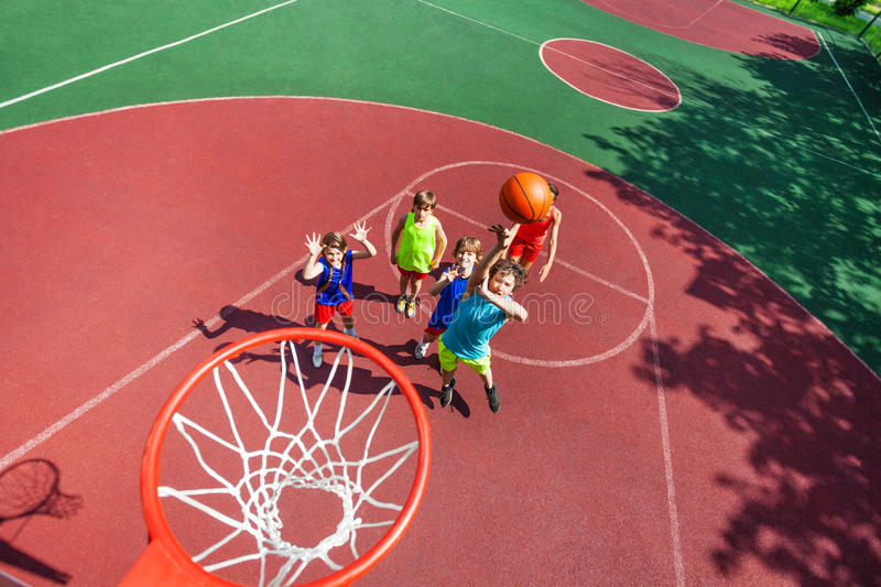 Kids stand on ground and ball flying to the basket. Kids standing on ground down and ball flying to the basket from top during basketball game stock photo