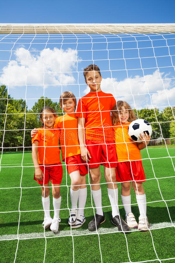 Kids stand in line with football behind woodwork stock image