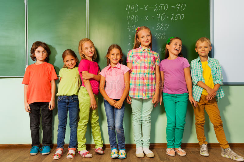 Kids stand in line near the blackboard and smile. Group of school kids stand in line near the blackboard during mathematics class and smile stock photos