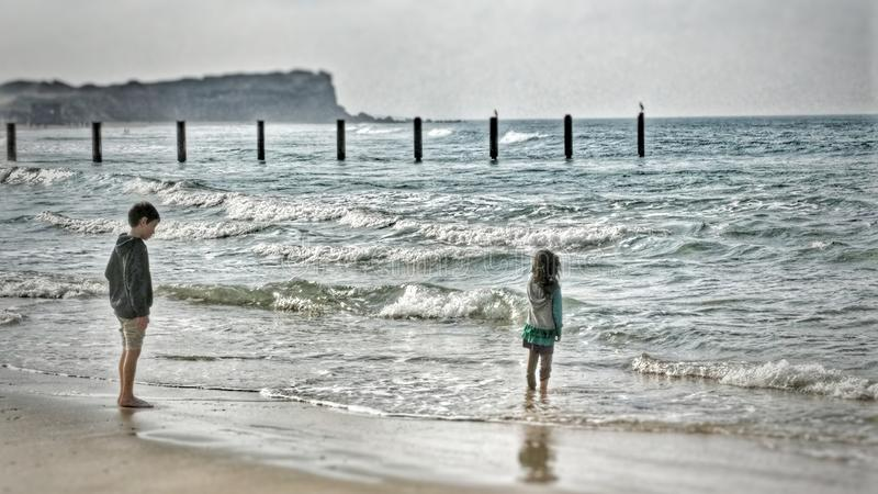Two young children standing on the beach watching the waves royalty free stock photo