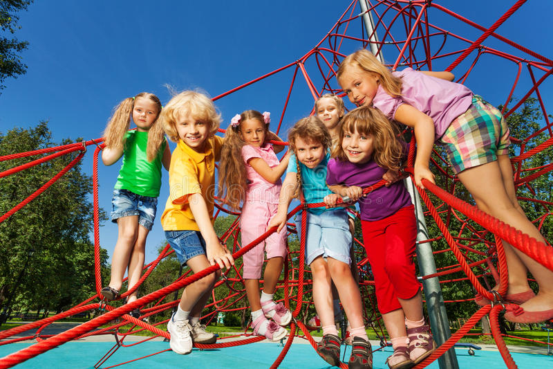 Kids standing in a row on red ropes of playground. Large group of kids standing in a row on red ropes of playground net in summer stock images