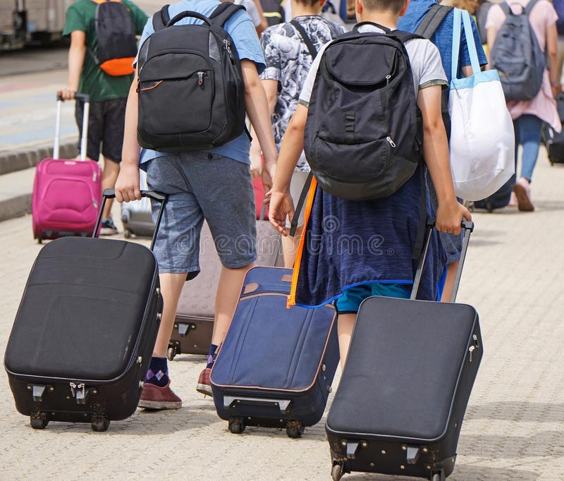 Kids on the street with luggage. In summer stock images