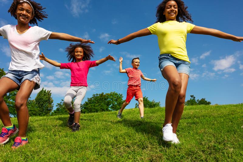 Kids with stretched hands run over grass field stock images