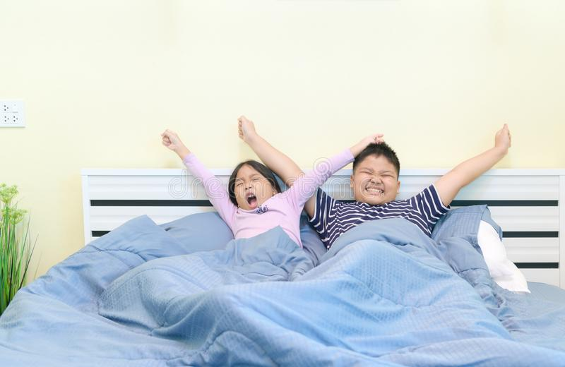 Kids are stretching in bed after waking up stock image