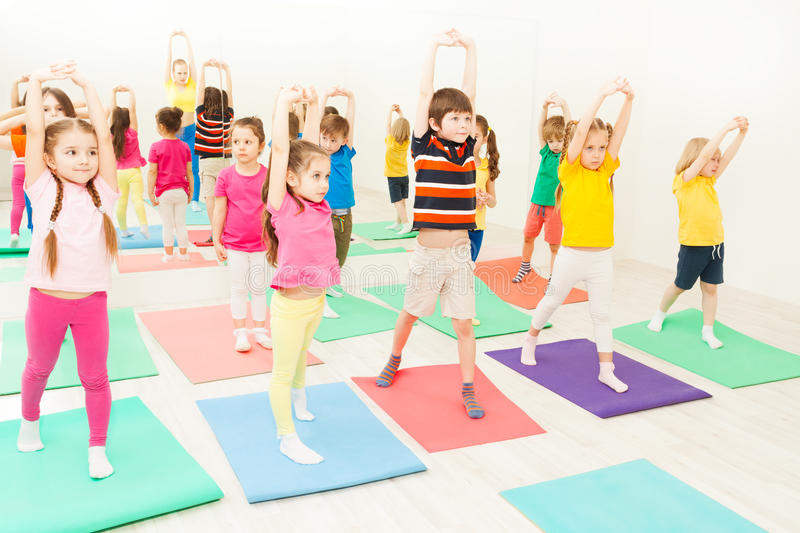 Kids stretching during gymnastic lesson in gym stock photography
