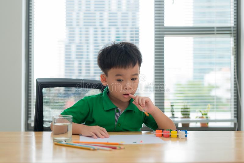 Kids at study table thinking.Kid holding a pen and a notebook with thinking face action.Boy doing homework at study table with. Thinking act royalty free stock photography