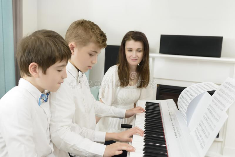 Kids Studying and Playing Piano in Tandem. Kids studying at electric piano instrument, playing in tandem, teacher next to them royalty free stock photo