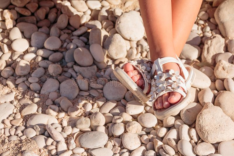 Kids summer sandals. baby shoes on stones beach. girl white fashion footwear, leather sandal ,moccasins.legs of stock photo