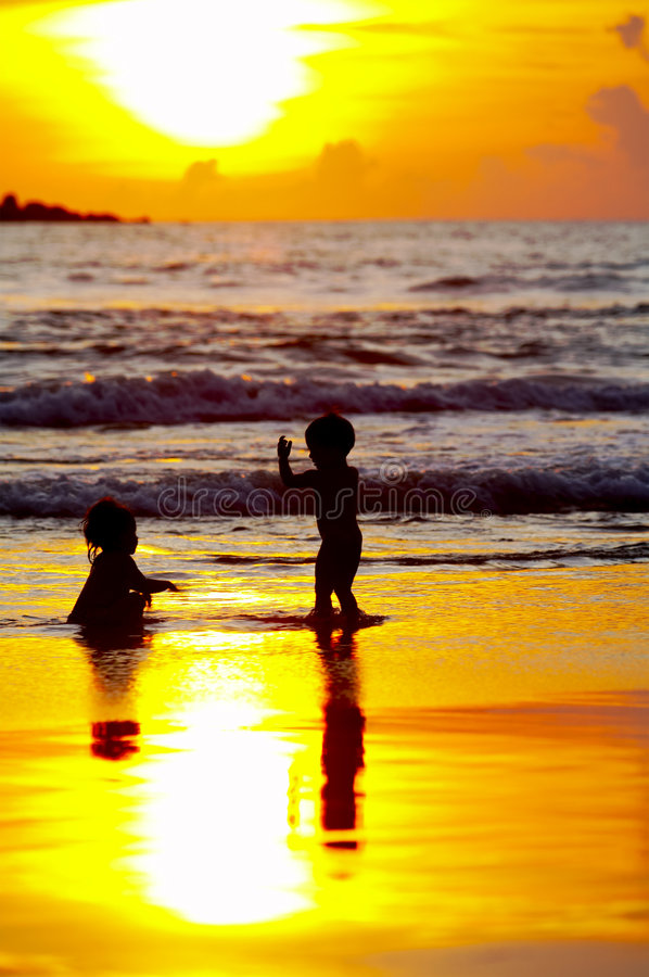 Kids sunset. View of two kid's silhouettes on the beach during sunset royalty free stock photo