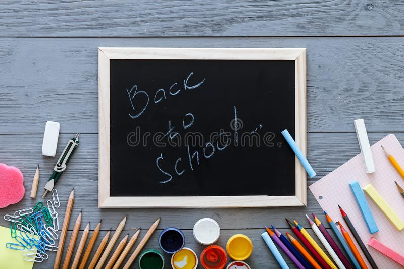Kids supplies on on grey wooden desk, back to school background written on chalkboard for modern primary education, new year start stock photography