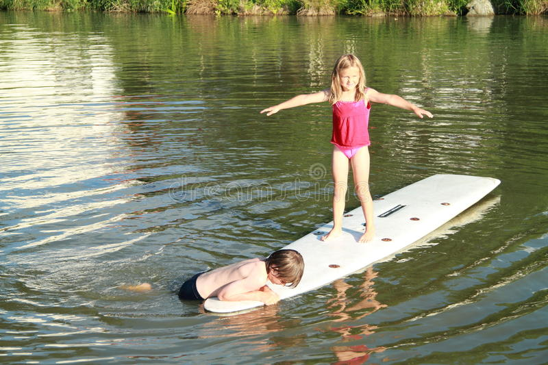 Kids on surf. Little girl in pink t-shirt standing on and a boy in blue shorts lying on a white surf board foating on pond royalty free stock images