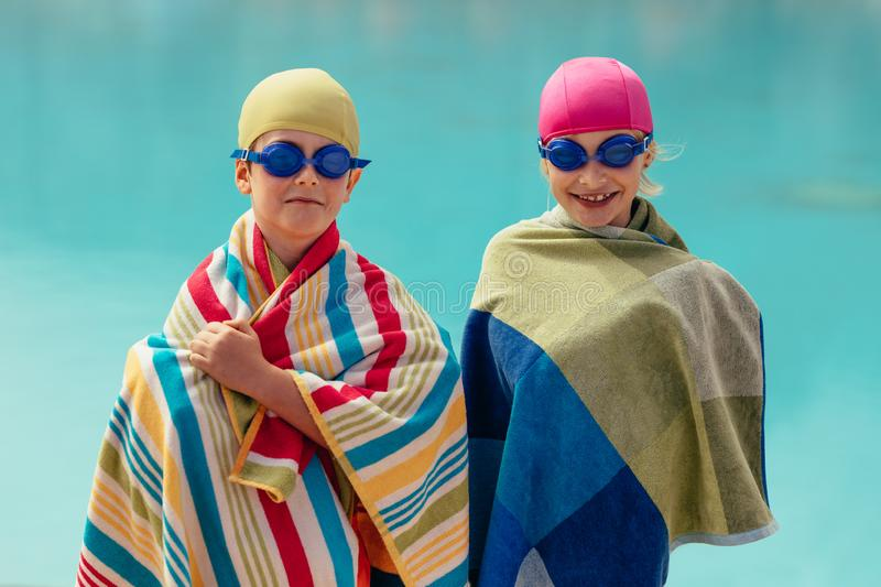 Kids after swimming lessons. Two kids wrapped in towel standing by pool. Boy and girl in swimming goggles and cap after swimming training royalty free stock image