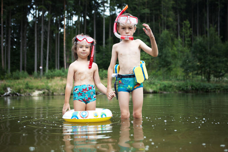 Kids swimming at pond. Two children swimming with floaters, masks and snorkels in a pond in a forest royalty free stock image