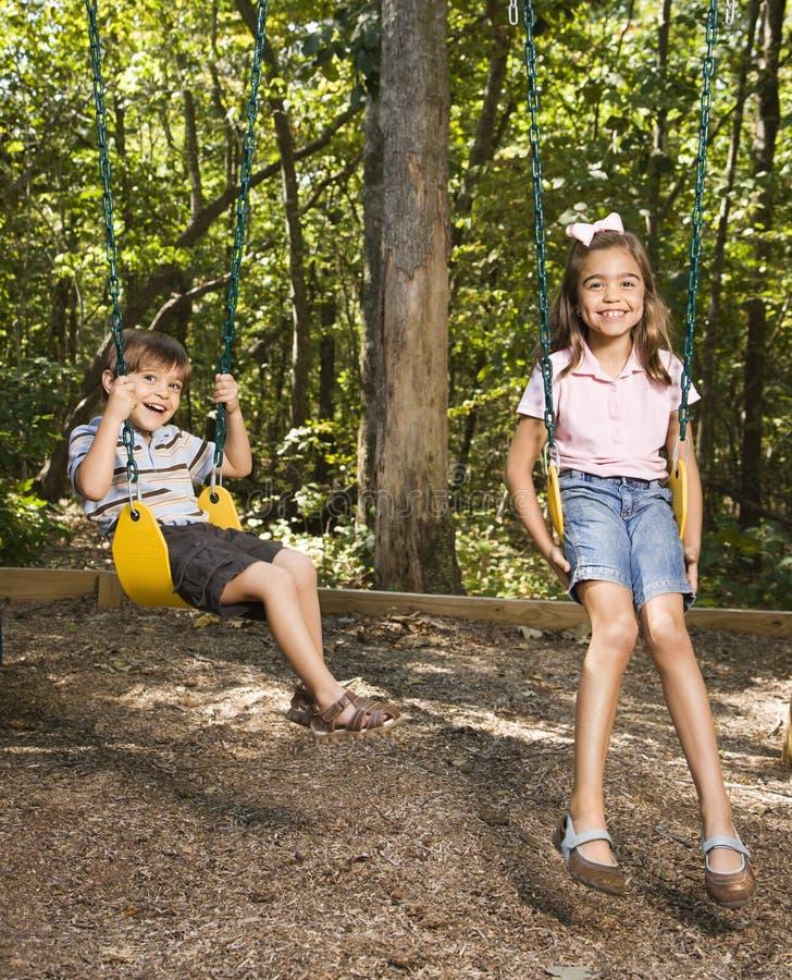 Kids on swing set. royalty free stock photos