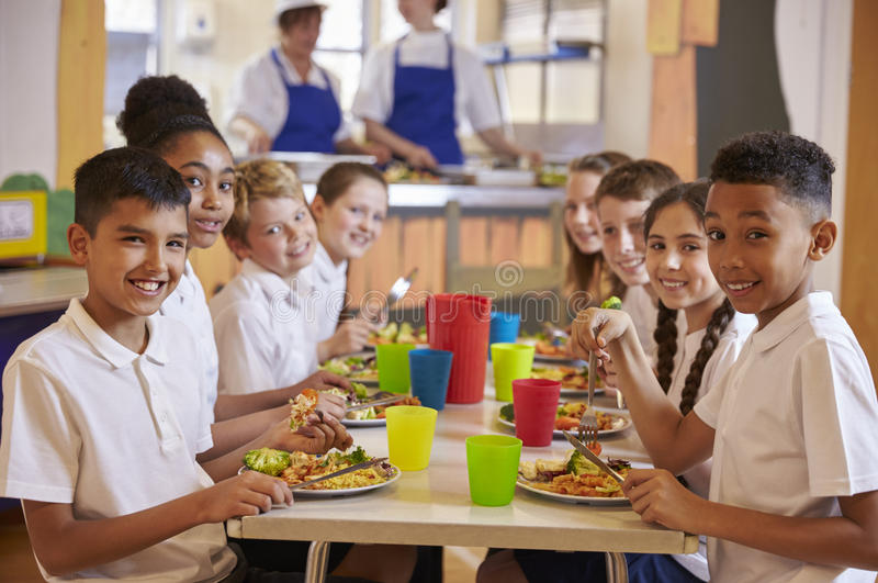 Kids at a table in a primary school cafeteria look to camera stock images