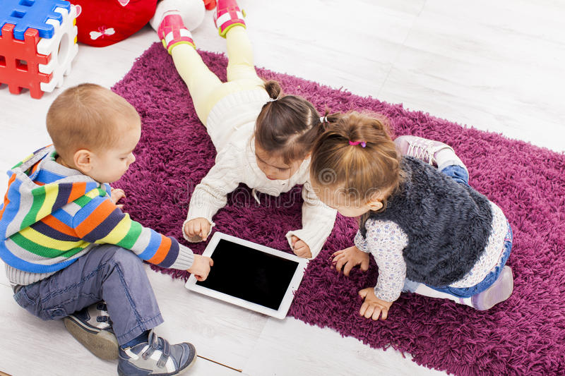 Kids with tablet. Kids working with tablet in the room stock photography