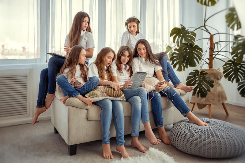 Kids with tablet pc computer communicate in social networks. Group of teenage girls is using gadgets. Education, friendship, technology and children concept stock image