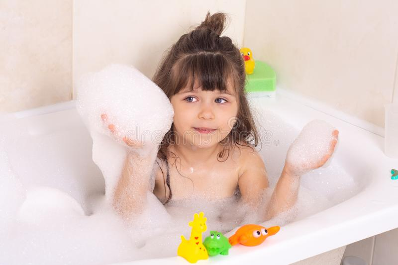 Kids taking bubble bath. Child bathing in bathtub. Little girl playing with water. Rubber toys in foam bath. Cute little baby girl taking bath playing with foam stock photos