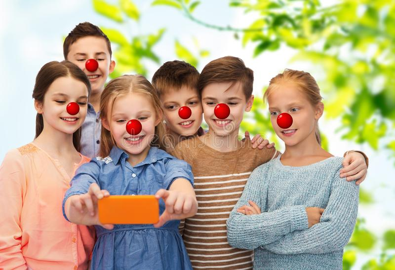 Kids taking selfie with smartphone at red nose day royalty free stock images