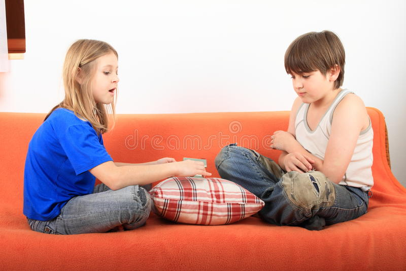 Kids talking about housing. Little girl and serious boy - kids talking about housing with a plastic house on pillow between them royalty free stock photos