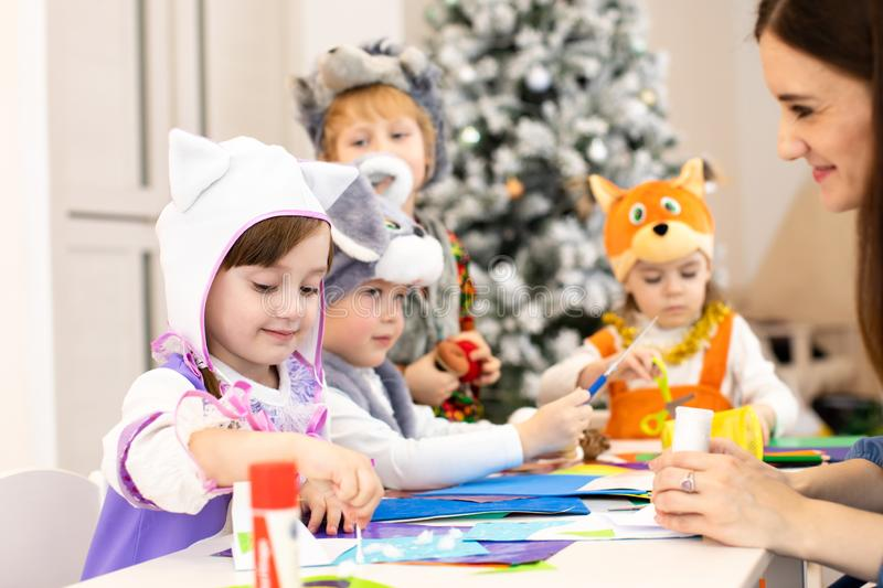 Kids with teacher make hands crafts in kindergarten. Children prepare to christmas. Group orf preschoolers on lesson in stock photos