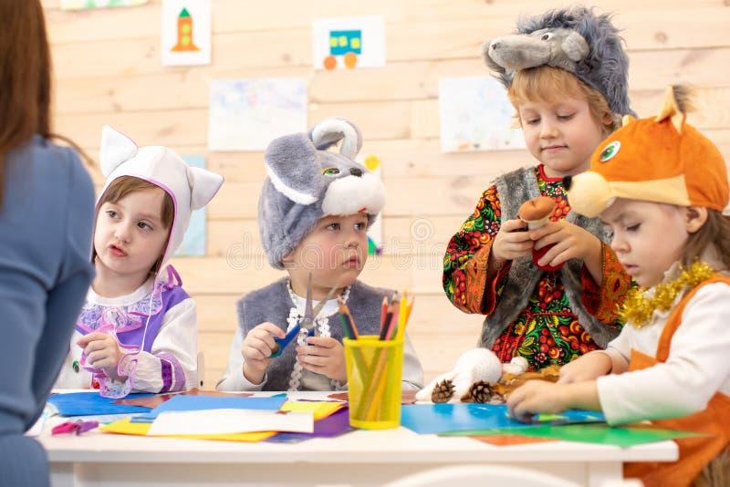 Kids with teacher make hands crafts in kindergarten. Children prepare to christmas. Group of preschoolers on lesson in stock photo