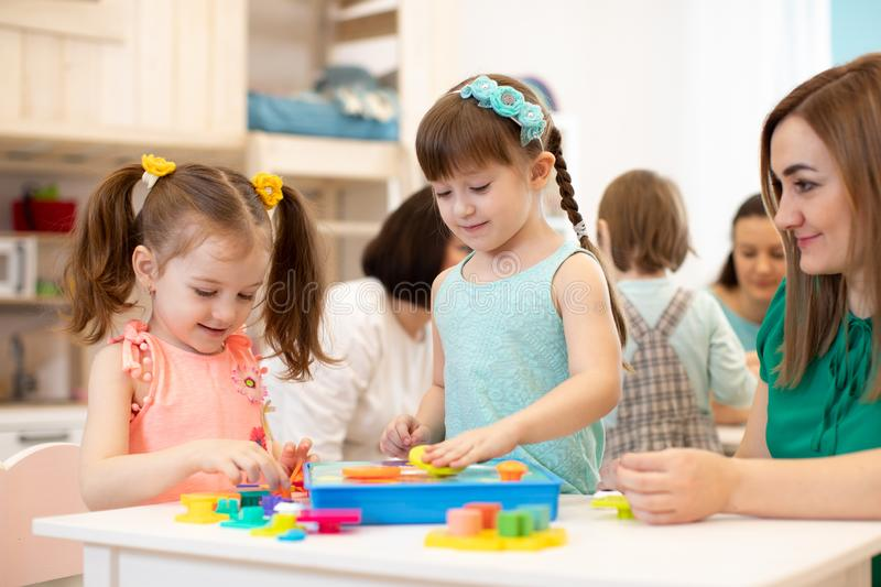 Kids with teacher playing with developmental toys in kindergarten stock images