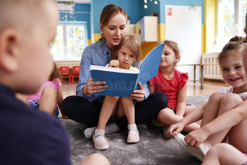 Kids and teacher reading a book together stock photo