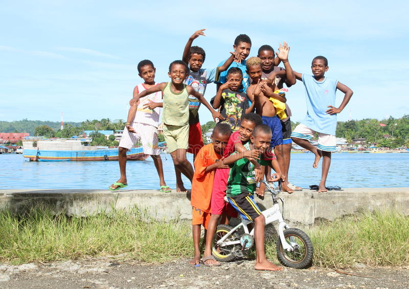 Kids and teens posing on bank of sea in Manokwari royalty free stock image