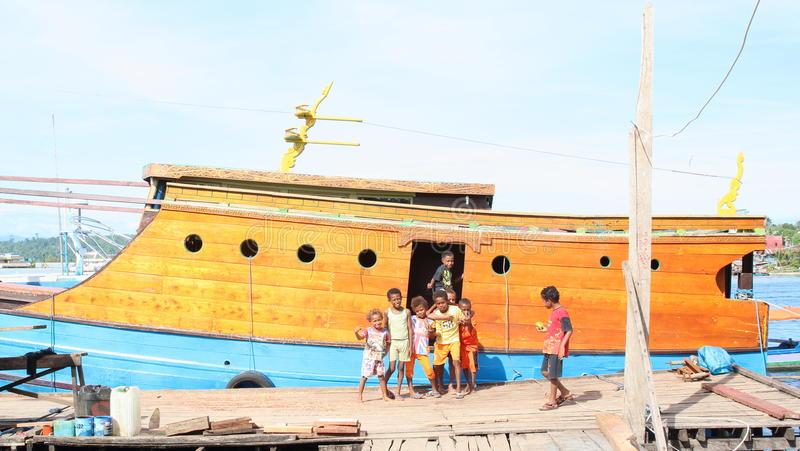 Kids and teens posing in front of traditional papuan ship stock images