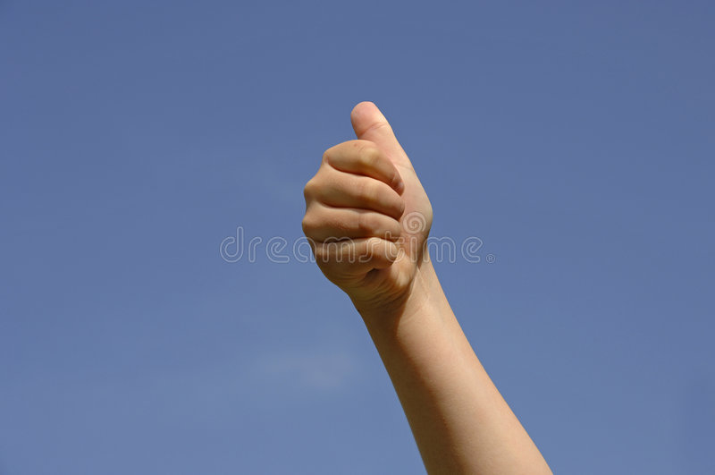 Kids thumb up. Of a caucasian white boy up to the blue sky background stock image