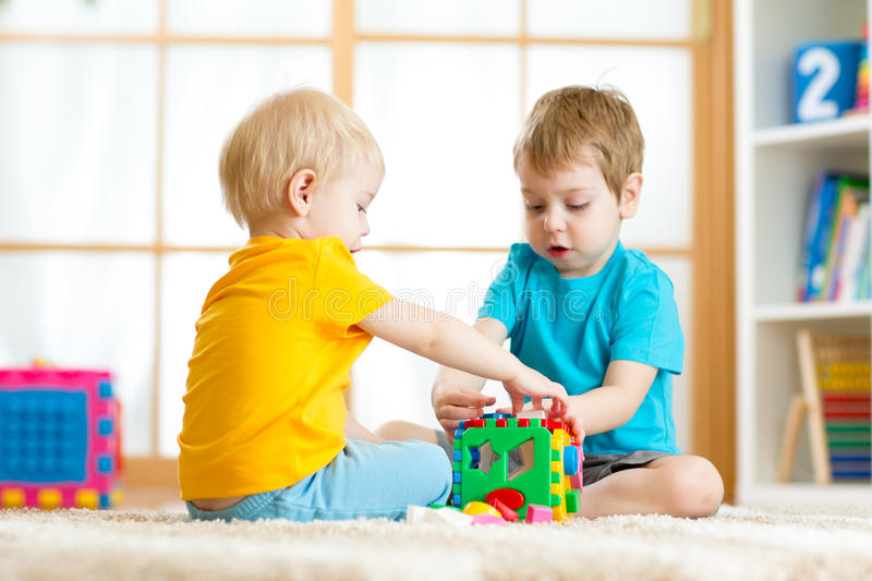 Kids toddler preschooler boys playing logical toy learning shapes and colors at home or nursery royalty free stock image