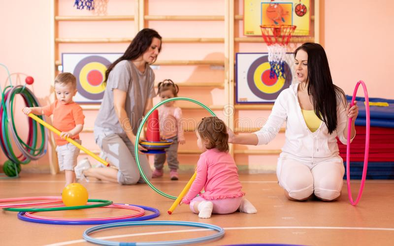 Kids toddlers play with hoops in kindergarten gym. Kids toddlers play with adults in kindergarten gym royalty free stock image