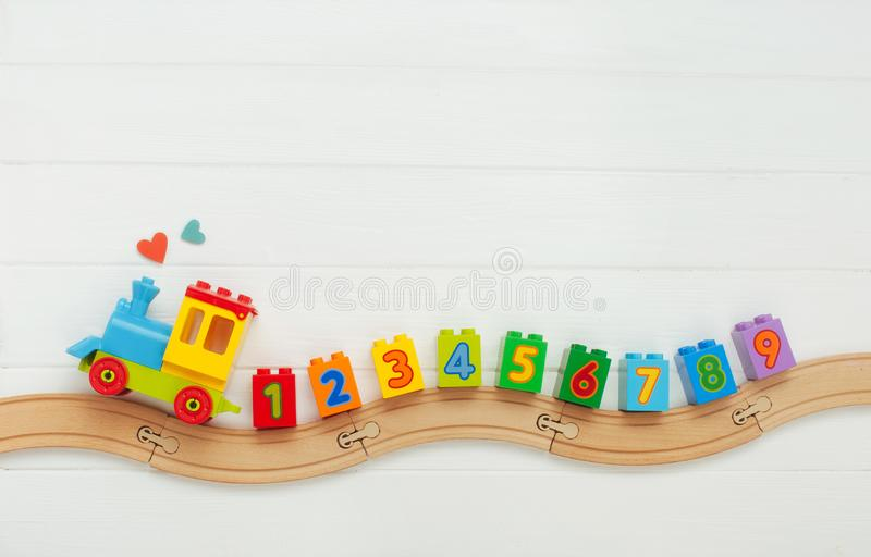 Kids toy train with numbers on railway on white wooden background with copy space royalty free stock image