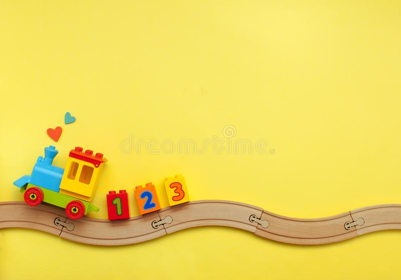 Kids toy train with numbers on toy wooden railway on yellow background with copy space. Toys background with copy space. Kids toy train with numbers on toy royalty free stock photography