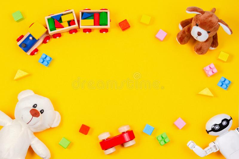Kids toys background. White teddy bear, wooden train, toy car, robot, colorful blocks on yellow background stock images