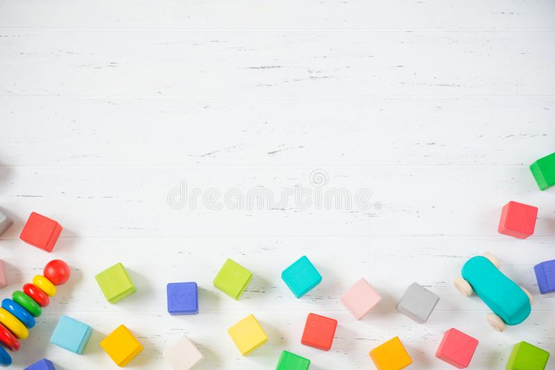 Kids toys frame wooden blocks, car, pyramidion on white wooden background. Top view. Copy space for text. Kids toys frame wooden blocks, car, pyramidion on stock photography
