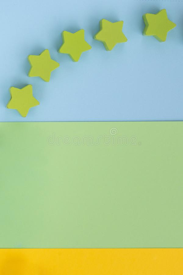 Kids toys on pastel blue green paper yellow background. Top view on children`s educational games. Wooden stars. Flat lay, copy. Space royalty free stock images
