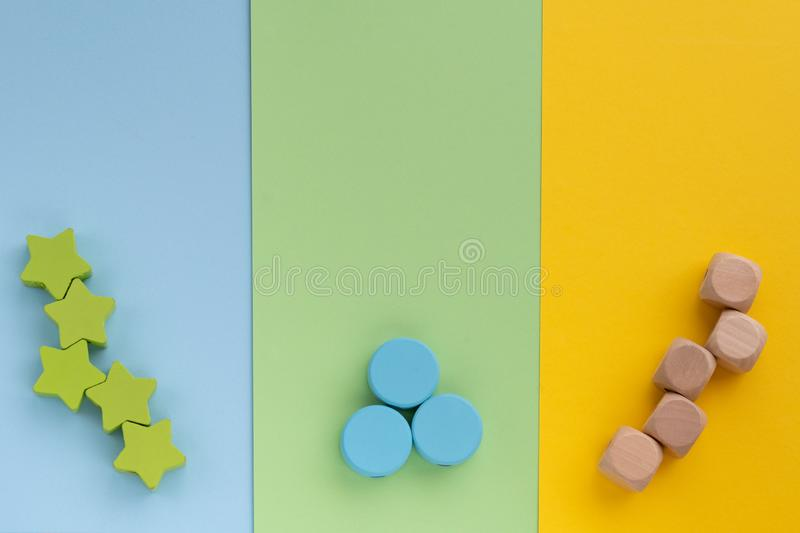 Kids toys on pastel yellow blue green paper background. Top view on children`s educational games. Wooden stars circles cubes. Fla. T lay, copy space royalty free stock images