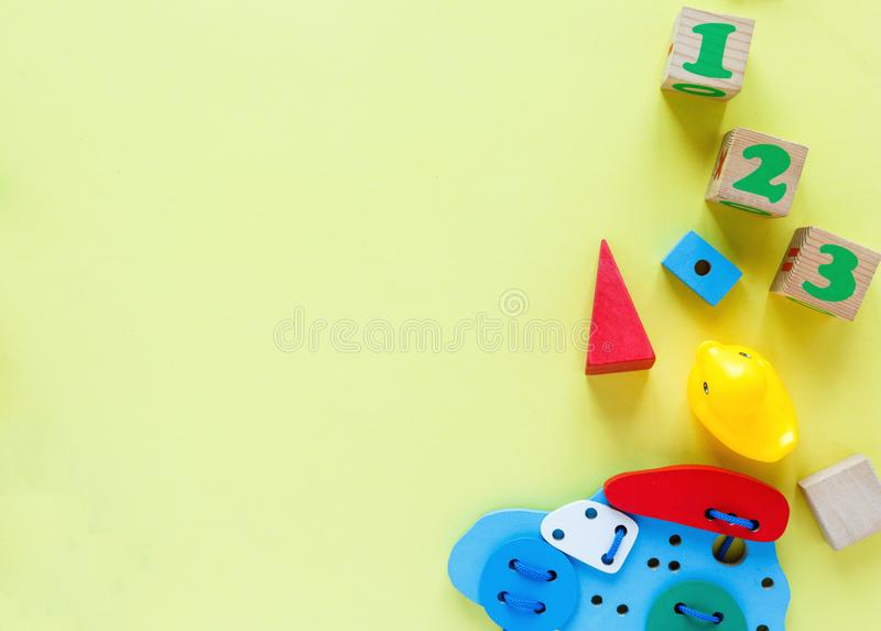 Kids toys: pyramid, wooden blocks, xylophone, train on white wooden background. Top view. Flat lay. stock images