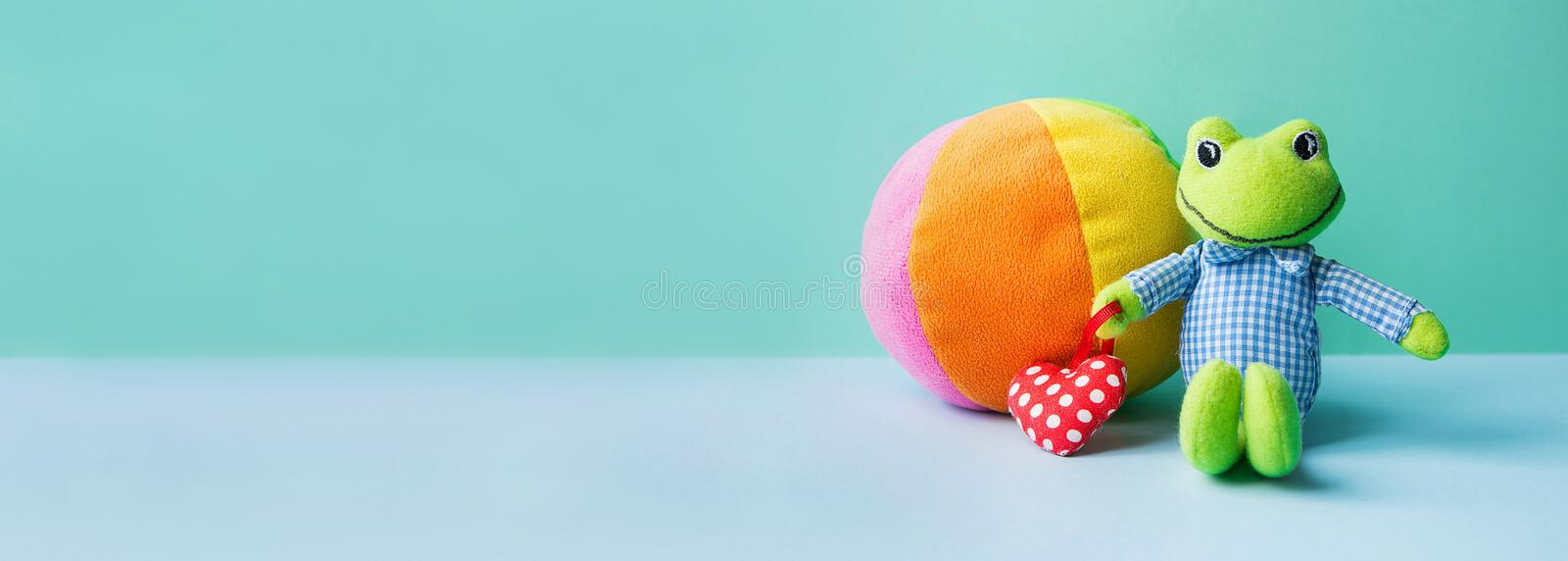 Kids Toys Small Frog Holding Red Heart Multicolored Textile Soft Ball on Blue Green Background. Banner Charity Nursery Hospital royalty free stock image