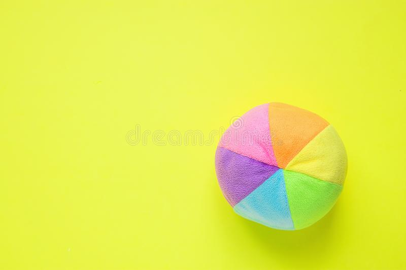 Kids Toys Small Plush Multicolored Textile Soft Ball on Yellow Background. Banner Placeholder Streamer Charity Nursery Hospital stock photography
