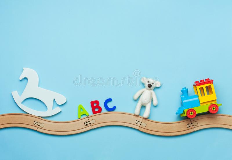 Kids toys on toy wooden railway on blue background with blank space for text. Toys background with copy space. Kids toys horse, ABC letters, bear and train on royalty free stock images