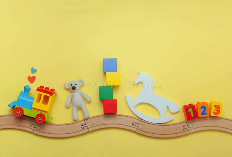 Kids toys on toy wooden railway on yellow background. Toys background with copy space. Kids toys train, bear, cubes, rocker horse and number blocks on toy wooden royalty free stock images